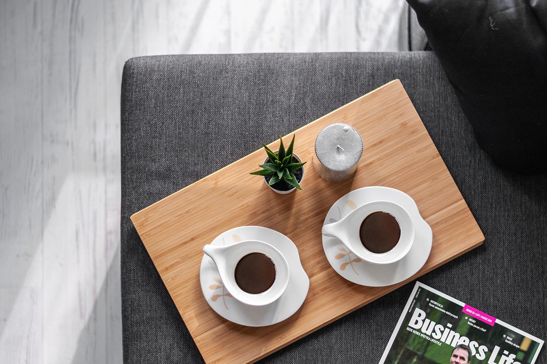 Zdjęcie wnętrza - widok z góry na filiżanki z kawą, kwiatek, drewnianą deskę i świece