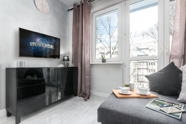 Zdjęcie wnętrza - czarna komoda, nad którą wisi telewizor