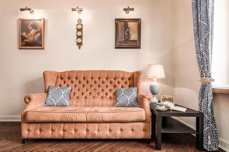 Zdjęcie wnętrza - antyczna kanapa obok drewnianego stolika kawowego