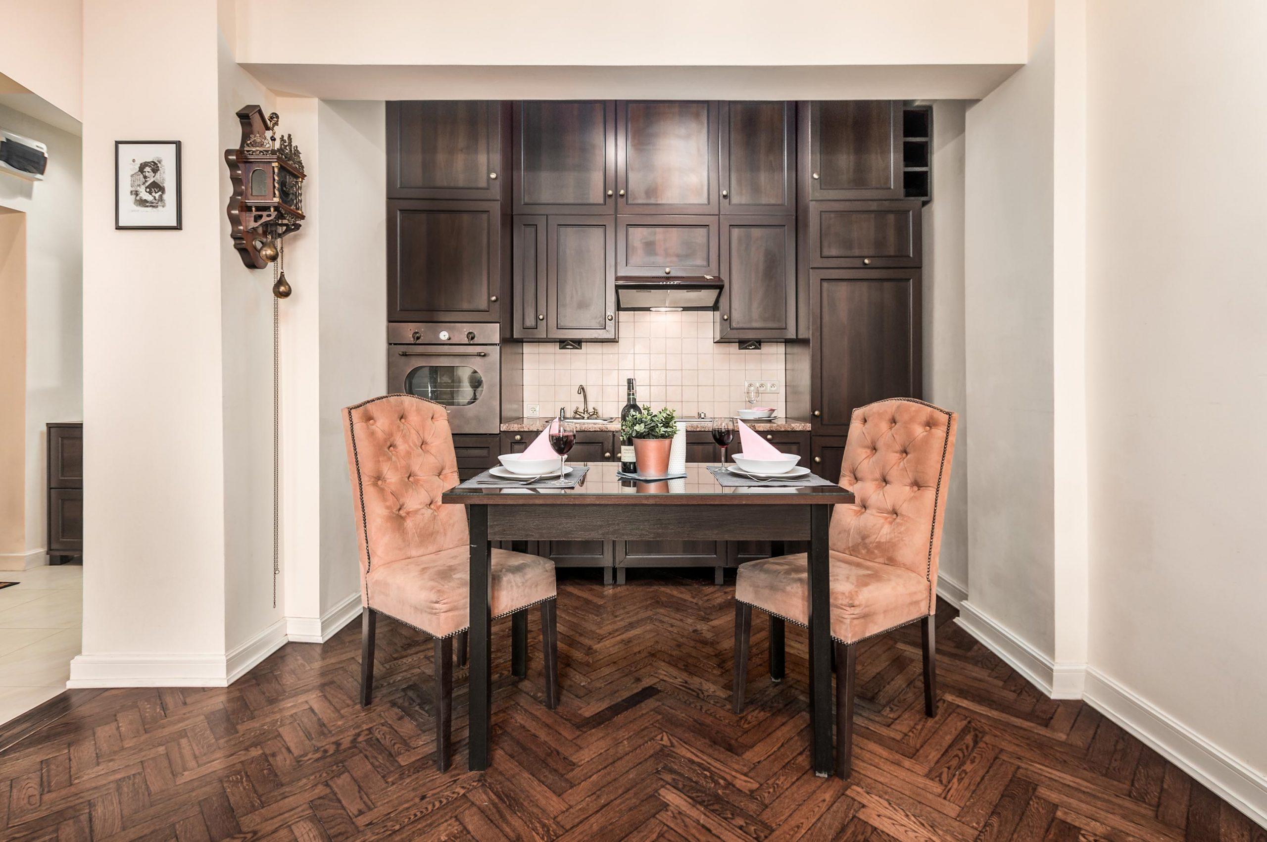 Zdjęcie wnętrza - zastawiony stół i aneks kuchenny z drewnianymi meblami