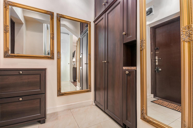 Zdjęcie wnętrza - korytarz z trzema lustrami i drewnianymi meblami