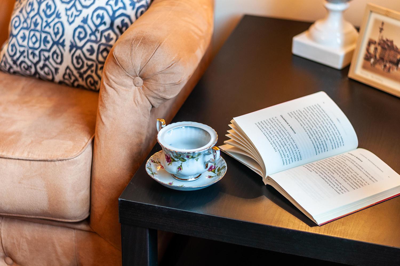 Zdjęcie wnętrza - filiżanka i otwarta książka na stoliku kawowym