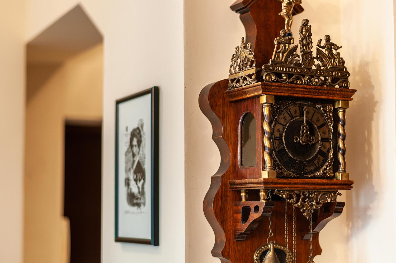 Zdjęcie wnętrza - antyczny drewniany zegar z mosiężnymi zdobieniami