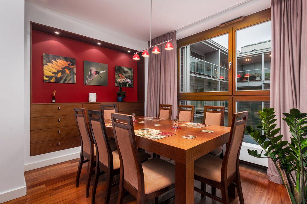 Zdjęcie wnętrza - drewniany stół w jadalni i czerwona ściana z obrazami