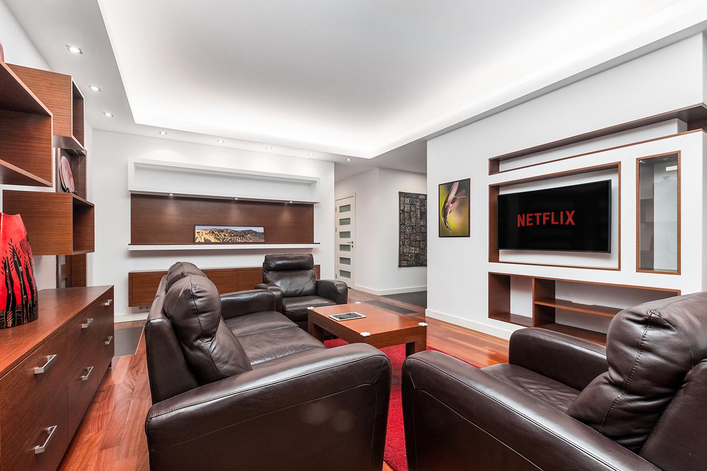 Zdjęcie wnętrza - salon ze skórzanymi fotelami i sofą, drewniane meble i wiszący na ścianie telewizor