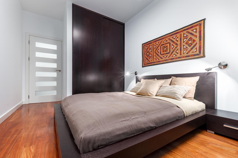 Zdjęcie wnętrza - dwuosobowe łóżko i drewniana szafa w sypialni