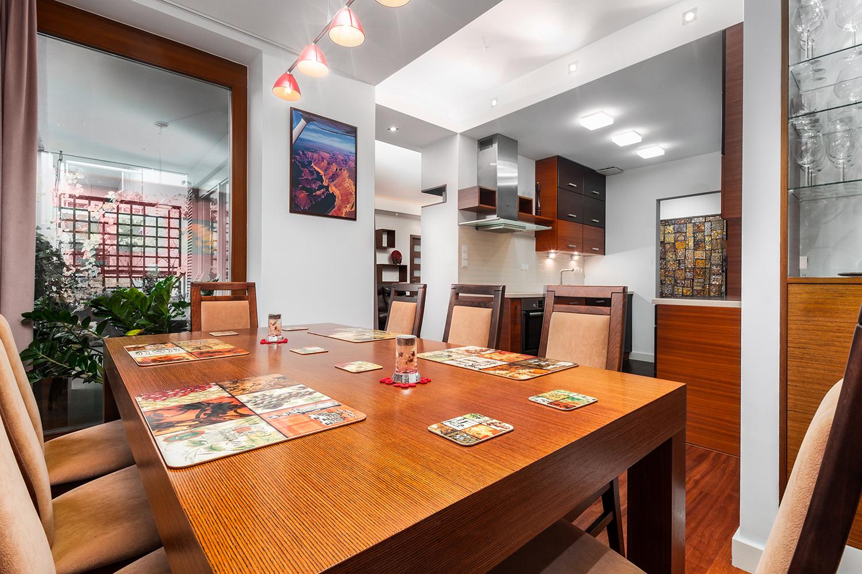 Zdjęcie wnętrza - drewniany stół w jadalni z widokiem na kuchnię
