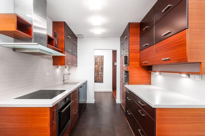 Zdjęcie wnętrza - kuchnia z drewnianymi meblami i białymi blatami