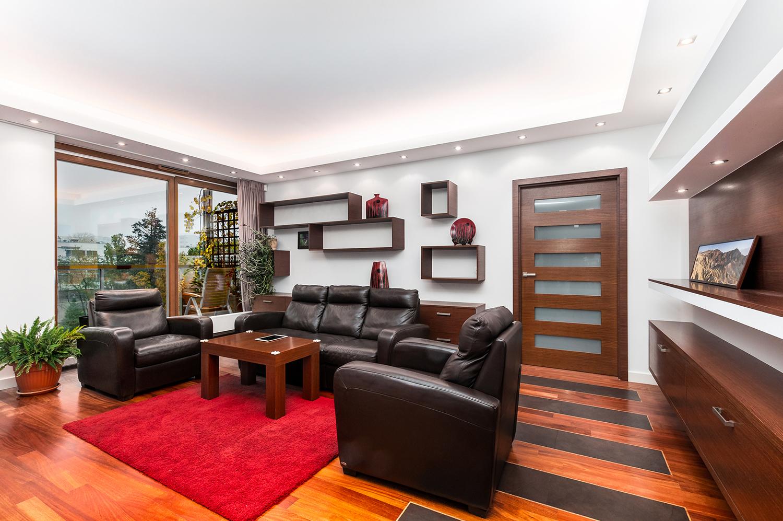 Zdjęcie wnętrza - salon z drewnianymi półkami, dużym oknem i skórzana sofa z dwoma fotelami