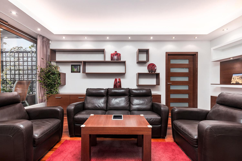 Zdjęcie wnętrza - salon z drewnianymi półkami i skórzana sofa z dwoma fotelami