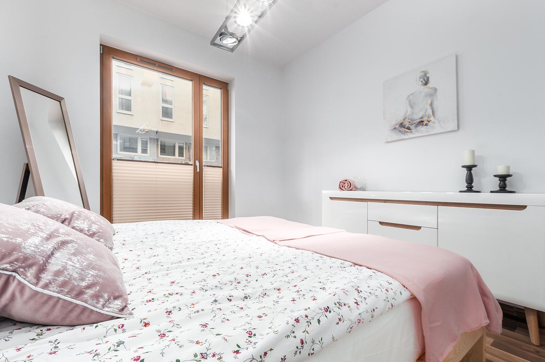 Zdjęcie wnętrza - jasne łóżko dwuosobowe w sypialni z białymi ścianami i okno