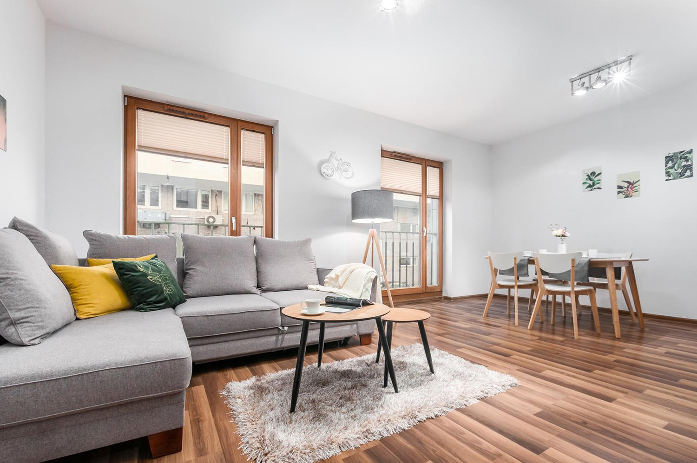 Zdjęcie wnętrza - widok na salon z drewnianą podłogą i dwoma oknami