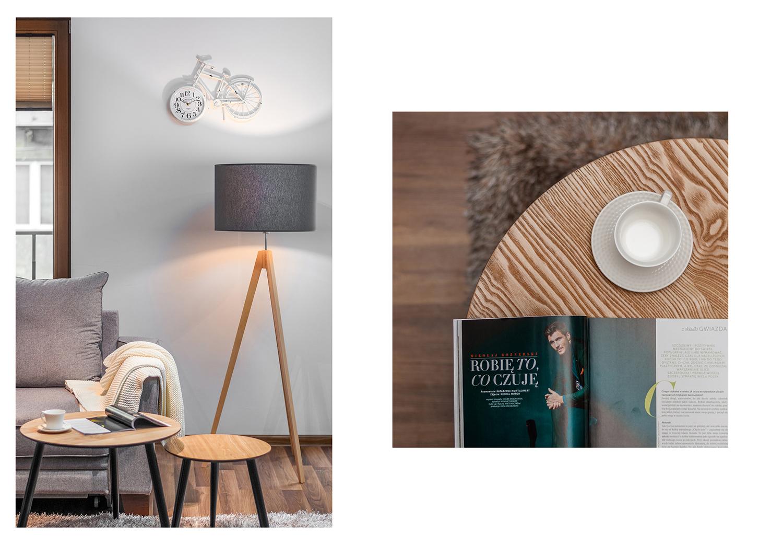 Zdjęcie wnętrza - drewniany stolik z gazetą i filiżanką koło szarej sofy i lampy