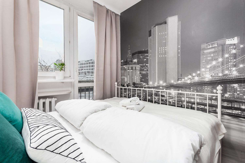 Zdjęcie wnętrza - sypialnia z dwuosobowym łóżkiem i fototapetą miasta na ścianie