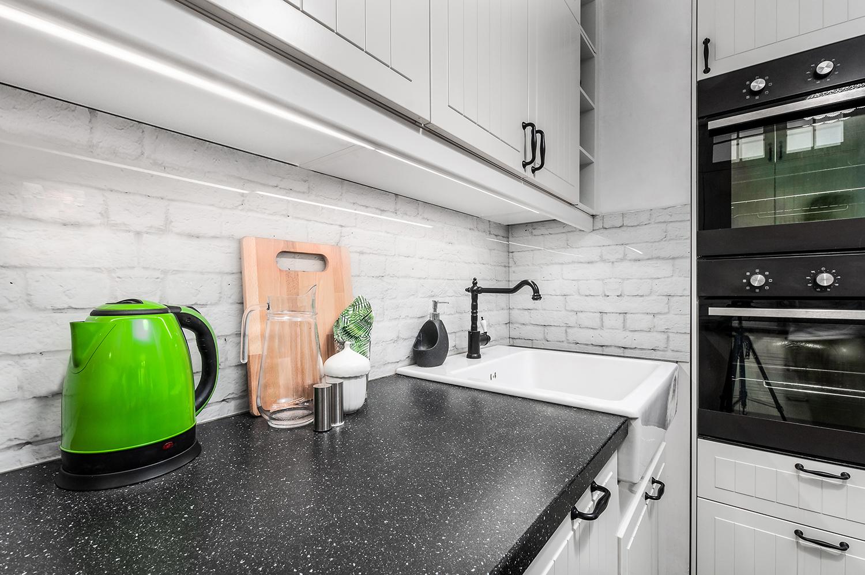 Zdjęcie wnętrza - czajnik na blacie kuchennym i umywalka ze zdobionym zlewem