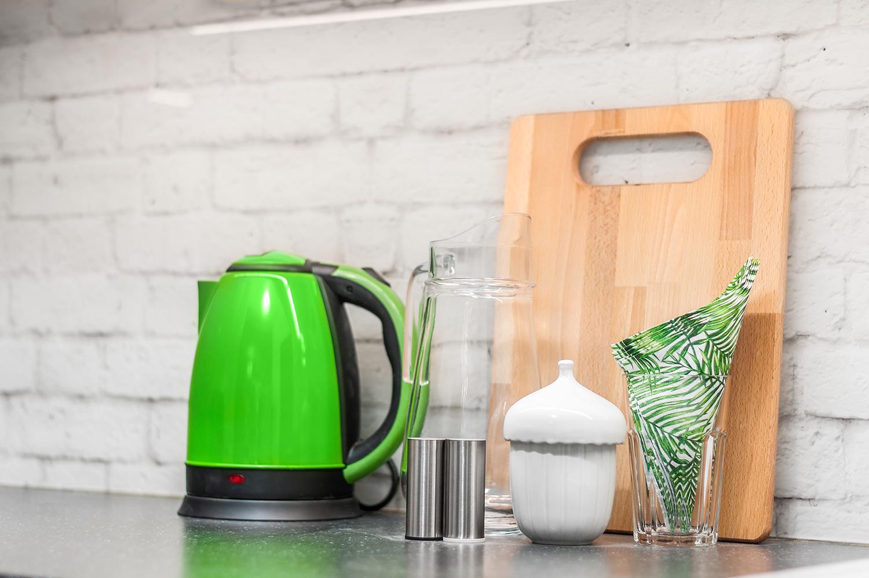 Zdjęcie wnętrza - czajnik, drewniana deska i cukiernica z dzbankiem na blacie w kuchni
