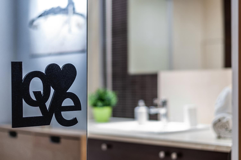 Zdjęcie wnętrza - napis love na lustrze przy wejściu do łazienki