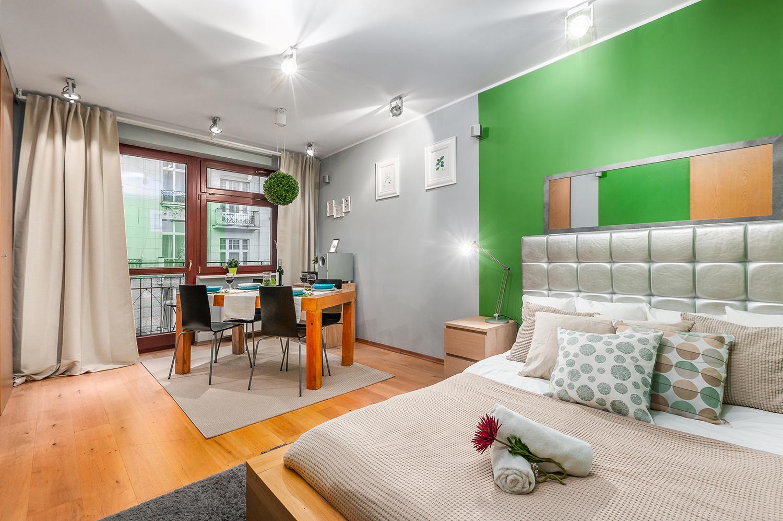 Zdjęcie wnętrza - łóżko i zastawiony stół w zielono szarym pokoju