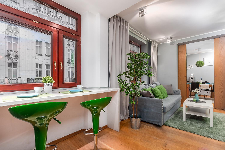 Zdjęcie wnętrza - dwa zielone hokery przy blacie i widok na salon i sypialnię