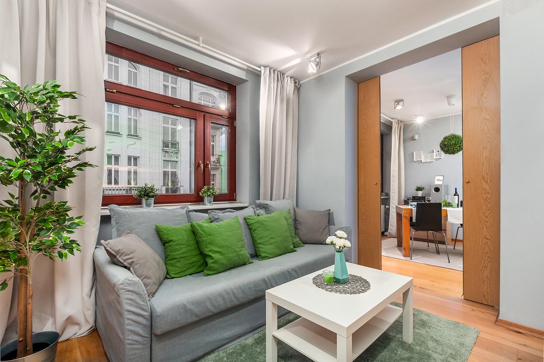 Zdjęcie wnętrza - sofa i stolik kawowy przy oknie w salonie z widokiem na sypialnię