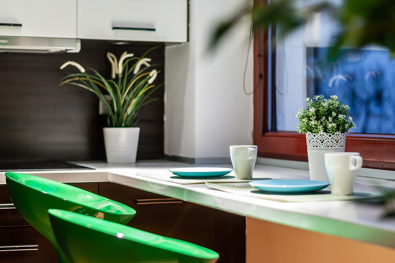 Zdjęcie wnętrza - filiżanki i talerze na blacie przy którym stoją dwa hokery