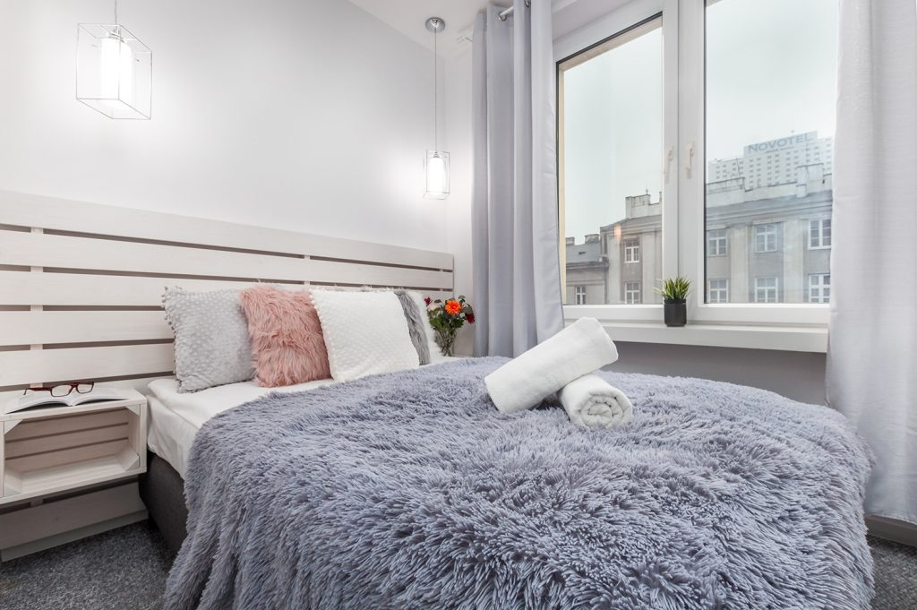 Zdjęcie wnętrza - łóżko z kocem z długim włosiem przy oknie w sypialni