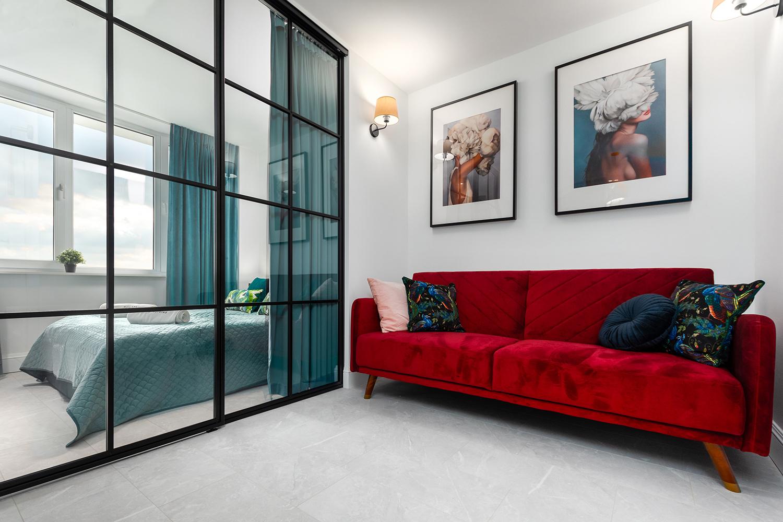 Zdjęcie wnętrza - czerwona sofa i przeszklone drzwi do sypialni