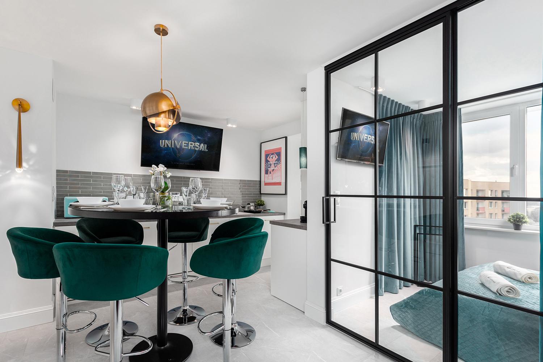 Zdjęcie wnętrza - okrągły zastawiony stół wraz z hokerami i przeszklone drzwi do sypialni