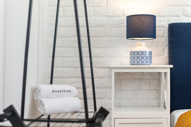 Zdjęcie wnętrza - lampka nocna przy łóżku i złożone ręczniki