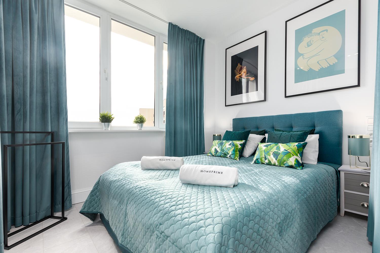 Zdjęcie wnętrza - dwuosobowe łóżko w sypialni z dużym oknem