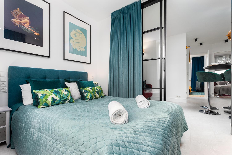 Zdjęcie wnętrza - duże łóżko w sypialni z widokiem na salon