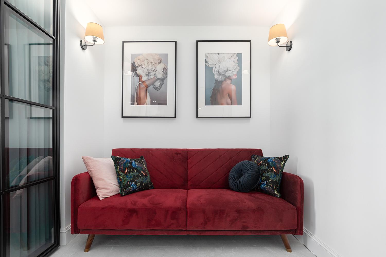 Zdjęcie wnętrza - czerwona sofa, nad którą wiszą dwa obrazy
