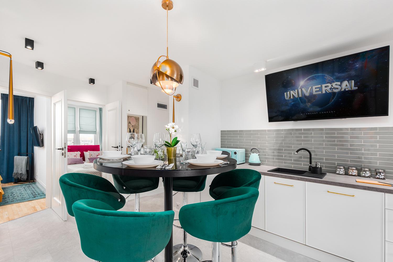 Zdjęcie wnętrza - okrągły zastawiony stół w jadalni i aneks kuchenny