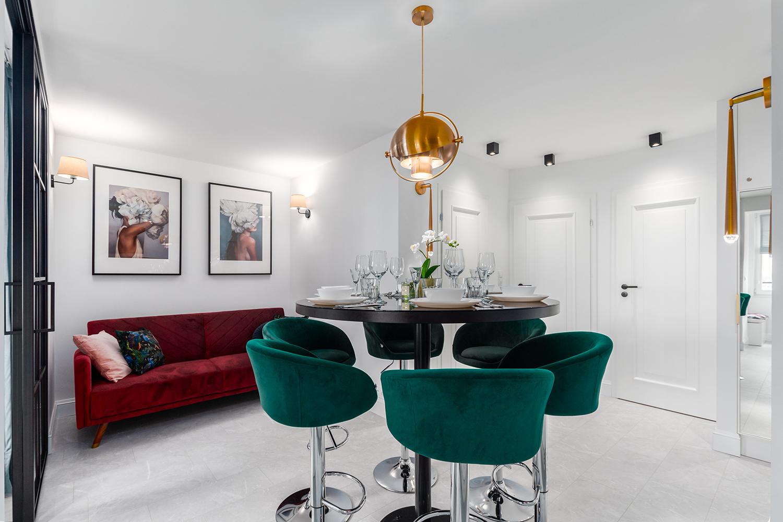 Zdjęcie wnętrza - okrągły zastawiony stół wraz z hokerami w salonie i czerwona sofa