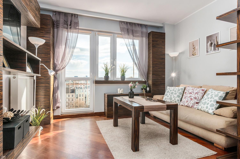 Zdjęcie wnętrza - salon z drewnianymi meblami, stół, sofa i okno