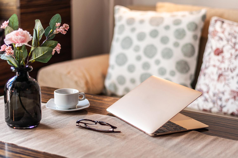 Zdjęcie wnętrza - różowy laptop, okulary, filiżanka i kwiaty w wazonie na drewnianym stole