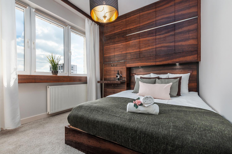 Zdjęcie wnętrza - sypialnia z dużym małżeńskim łóżkiem i drewniana szafa