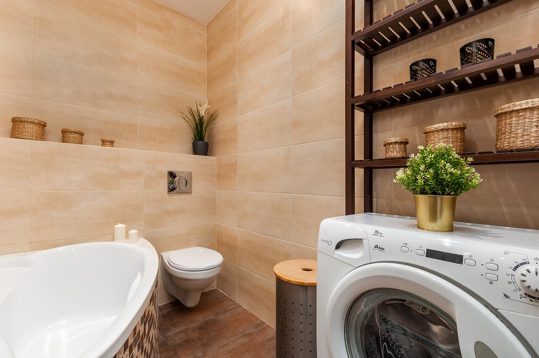 Zdjęcie wnętrza - beżowe płytki w łazience, pralka z kwiatkiem i wanna