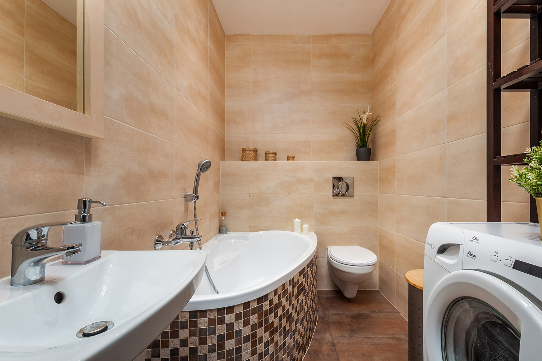 Zdjęcie wnętrza - łazienka z beżowymi płytkami, pralka , umywalka i wanna