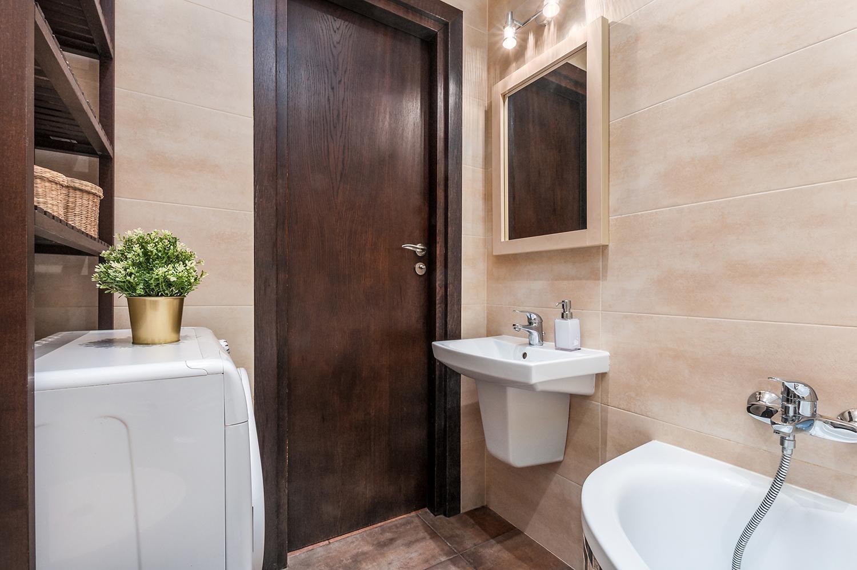 Zdjęcie wnętrza - łazienka z beżowymi płytkami i drewnianymi drzwiami oraz umywalka i pralka