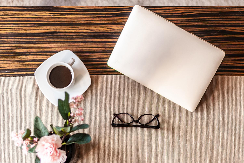Zdjęcie wnętrza - różowy laptop, okulary, filiżanka kawy i kwiaty w wazonie na drewnianym stole