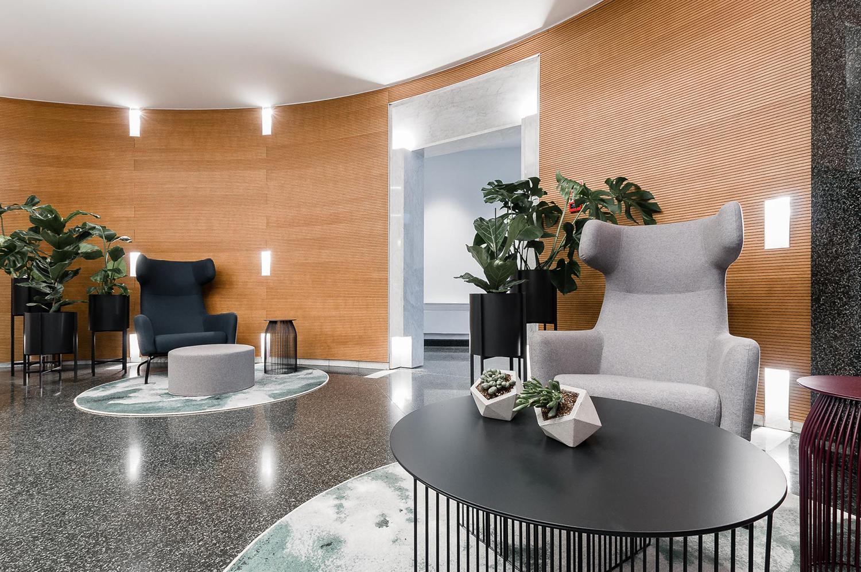 Zdjęcie wnętrza - szary fotel z metalowym stolikiem na tle drewnianej ściany