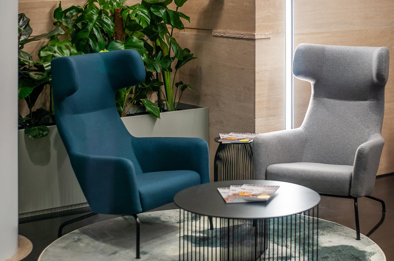 Zdjęcie wnętrza - dwa fotele przy stoliku kawowym z gazetami