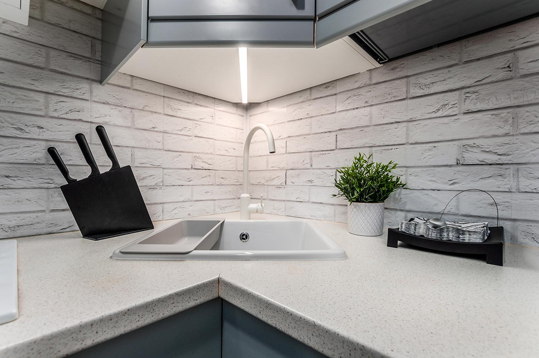 Zdjęcie wnętrza - zlew, kwiatek i zestaw noży w kuchni