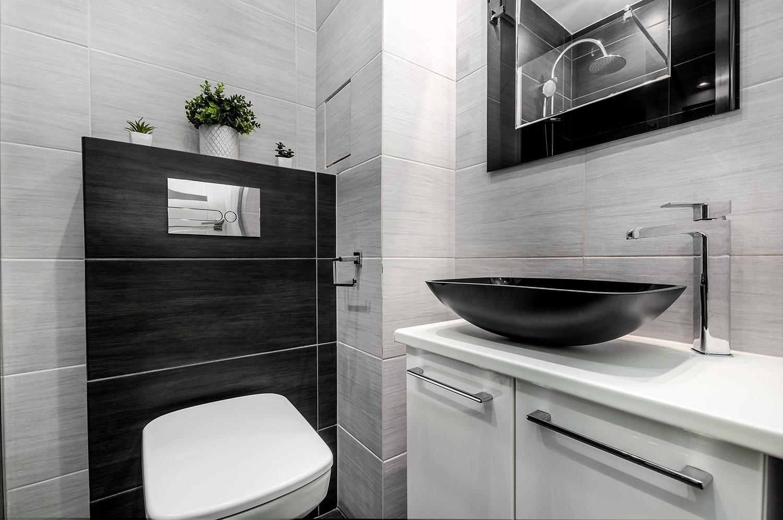 Zdjęcie wnętrza - czarny zlew pod lustrem i toaleta w łazience