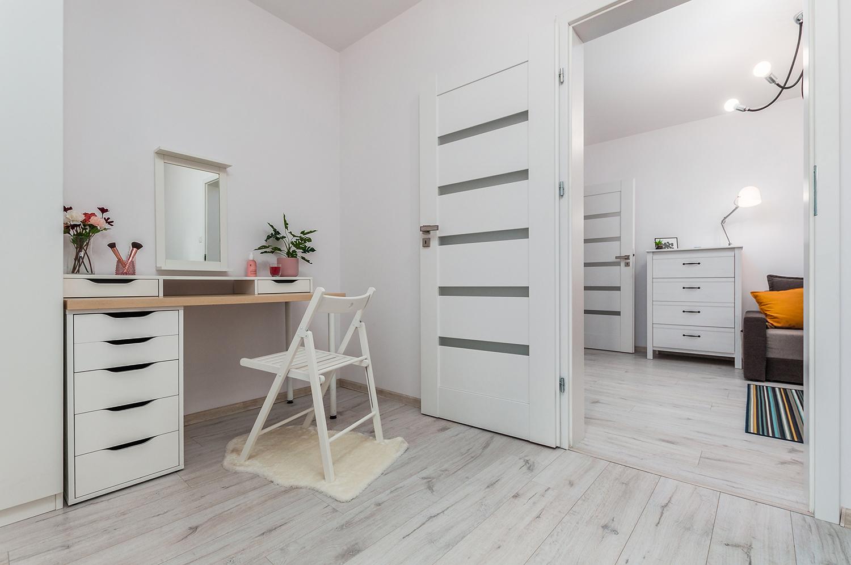 Zdjęcie wnętrza - biurko z drewnianym krzesłem i widok na salon