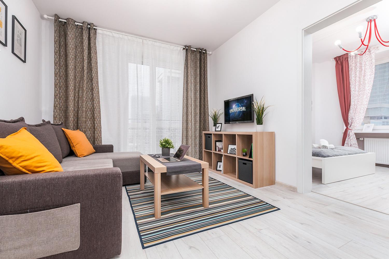 Zdjęcie wnętrza - salon z dużą sofą stolikiem i wiszący na ścianie telewizor