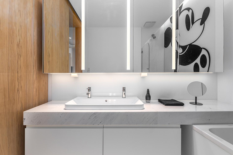 Zdjęcie wnętrza - jasna duża łazienka z wizerunkiem myszki Mickey i lustro nad umywalką