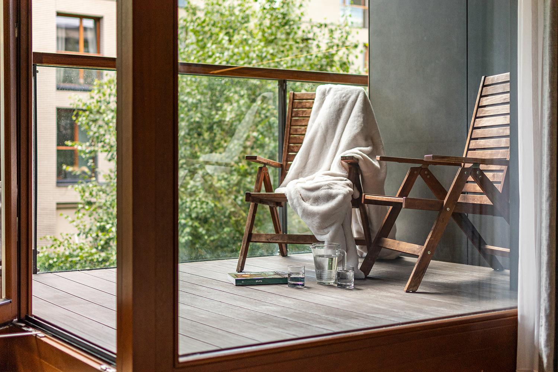 Zdjęcie wnętrza - dwa drewniane krzesła za szybą na tarasie
