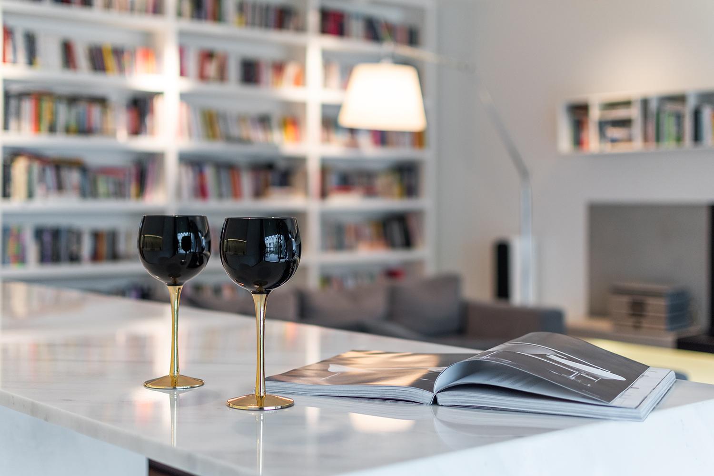 Zdjęcie wnętrza - dwa kieliszki do wina i otwarte czasopismo na marmurowym blacie